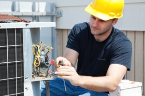 electrical repairman fixing an industrial air conditioning compressor